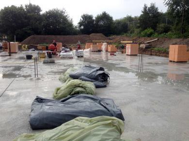 Drei Tage später wird die Folie zurück geschlagen und die Bodenplatte gewässert. Nun wird das Mauerwerk angelegt.